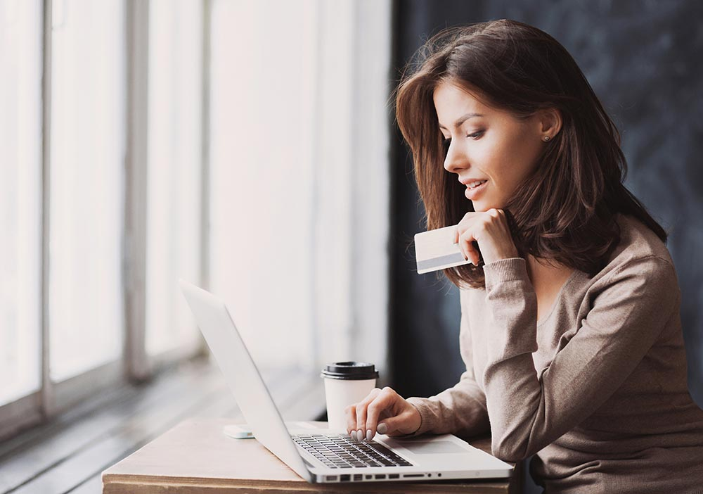 Young woman holding credit card and using laptop computer. Onlin