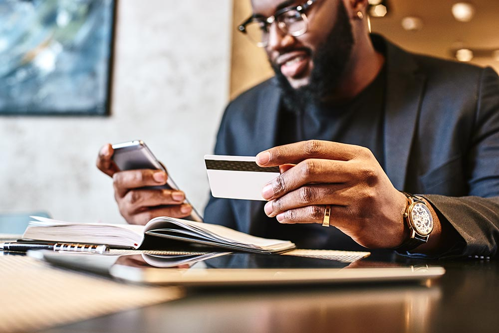 Shot of african american businessman holding mobile and credit card, while resting in the cafe